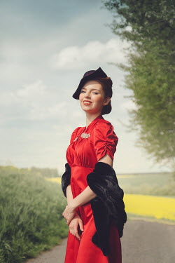 Joanna Czogala HAPPY RETRO WOMAN WITH HAT ON COUNTRY ROAD