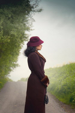 Joanna Czogala RETRO WOMAN WITH HAT ON COUNTRY ROAD