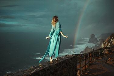 Katerina Klio WOMAN IN SILK DRESS ON SEA WALL WITH RAINBOW