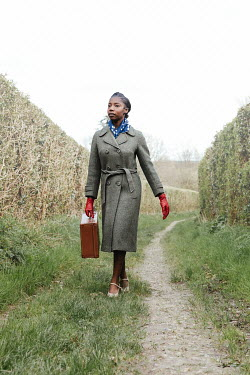 Matilda Delves RETRO WOMAN CARRYING SUITCASE ON COUNTRY LANE