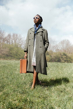 Matilda Delves WOMAN WITH COAT SUNGLASSES AND SUITCASE IN FIELD