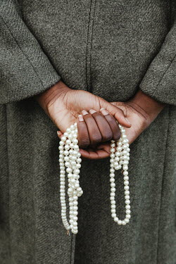 Matilda Delves WOMAN CARRYING PEARL NECKLACE BEHIND BACK