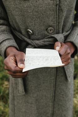 Matilda Delves BLACK WOMAN READING LETTER OUTDOORS