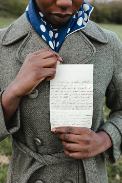 Matilda Delves RETRO WOMAN IN COAT HOLDING LETTER OUTDOORS