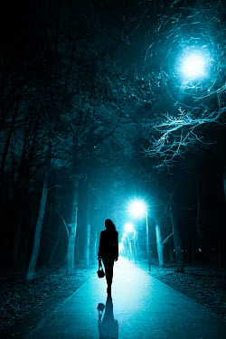 Magdalena Russocka silhouette of modern woman walking down park alley at night