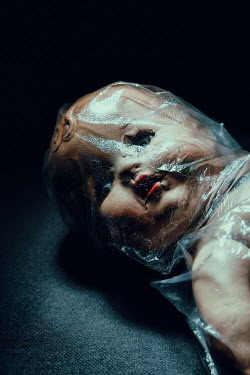 Magdalena Russocka close up of creepy vintage doll wrapped with plastic bag