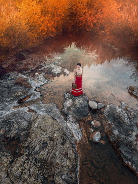 Mary Wethey HISTORICAL WOMAN STANDING BY POND IN AUTUMN
