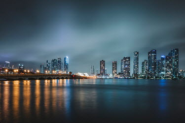 Evelina Kremsdorf HIGH-RISE BUILDINGS AND BRIDGE BY WATER WITH LIGHTS