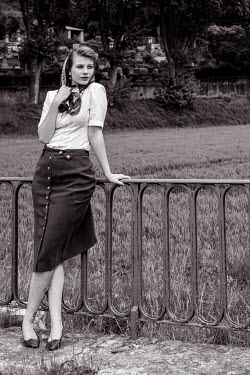 Elly De Vries RETRO WOMAN STANDING BY FIELD WITH FENCE