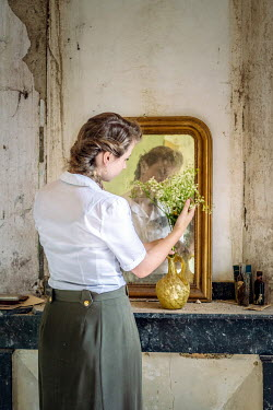 Elly De Vries WOMAN ARRANGING FLOWERS BY MIRROR INDOORS
