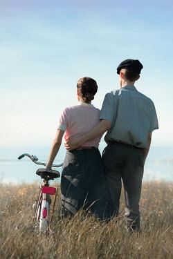 Ildiko Neer Vintage couple standing by lake with bicycle