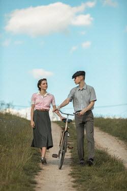Ildiko Neer Vintage couple walking on country road with bicycle