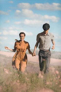 Ildiko Neer Vintage couple running in meadow