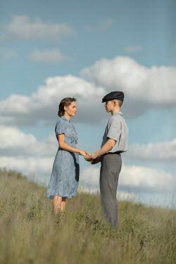 Ildiko Neer Vintage couple standing in field hand in hand