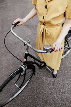 Matilda Delves RETRO WOMAN IN YELLOW DRESS WITH BICYCLE