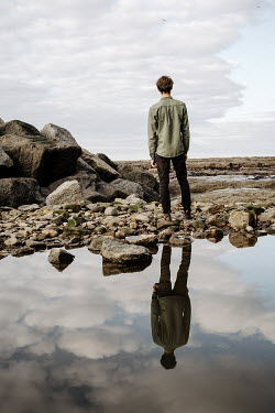 Esme Mai MAN STANDING BY ROCK POOL WITH REFLECTION