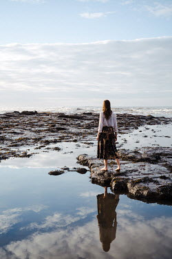 Esme Mai WOMAN STANDING BY ROCK POOL WITH REFLECTION