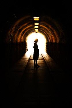Nikaa SILHOUETTED WOMAN STANDING IN DARK TUNNEL