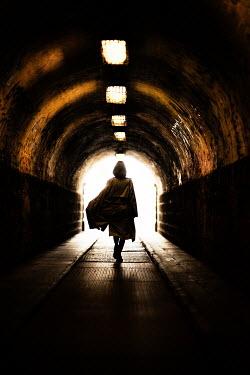 Nikaa WOMAN WALKING IN DARK TUNNEL