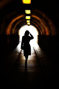 Nikaa SILHOUETTED WOMAN WALKING IN DARK TUNNEL