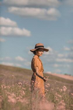 Ildiko Neer Young woman touching flower in meadow