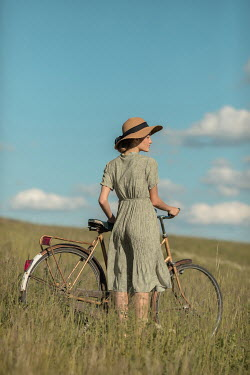 Ildiko Neer Young woman with bicycle in meadow