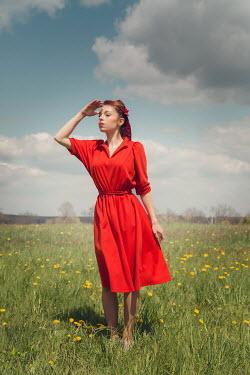 Joanna Czogala RETRO WOMAN IN RED STANDING IN FIELD