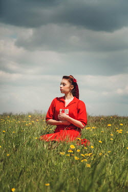 Joanna Czogala WOMAN IN RED SITTING IN FIELD WITH LETTERS