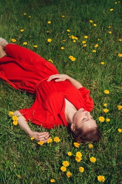 Joanna Czogala WOMAN IN RED DRESS LYING IN FIELD WITH DANDELIONS