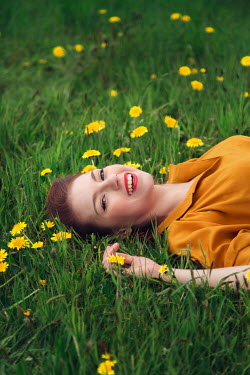 Joanna Czogala HAPPY WOMAN LYING IN FIELD WITH DANDELIONS