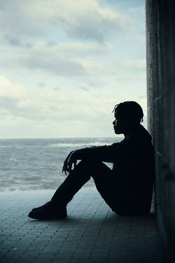Magdalena Russocka young man sitting against wall by sea