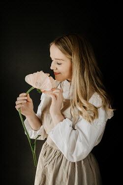 Esme Mai HAPPY BLONDE WOMAN SMELLING LARGE FLOWER