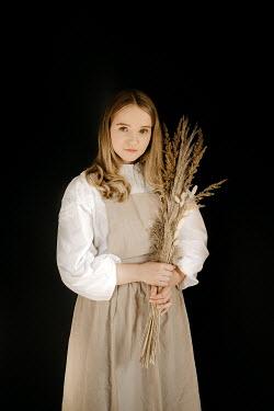 Esme Mai BLONDE WOMAN STANDING HOLDING GRASSES