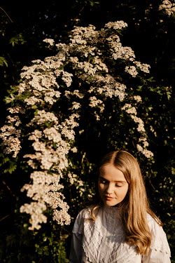 Esme Mai BLONDE WOMAN BY BUSH WITH WHITE FLOWERS
