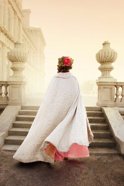 ILINA SIMEONOVA HISTORICAL WOMAN IN CAPE ON STEPS OUTSIDE GRAND HOUSE