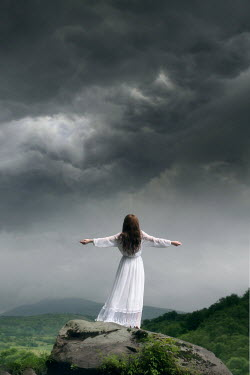 ILINA SIMEONOVA WOMAN IN WHITE ON CLIFF WITH STORY SKY