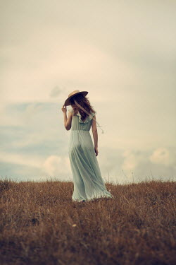 Magdalena Russocka young woman wearing long dress and straw hat standing in field
