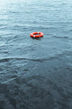 Magdalena Russocka orange lifebuoy floating on water