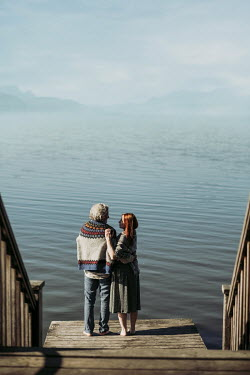 Magdalena Russocka middle aged couple standing on deck by lake