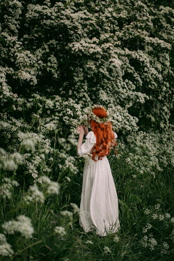 Rebecca Stice WOMAN WITH RED HAIR AND GARLAND STANDING BY BUSH