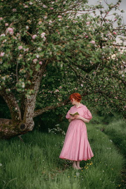 Rebecca Stice WOMAN WITH RED HAIR AND BOOK STANDING IN COUNTRYSIDE