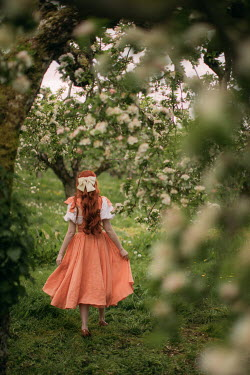 Rebecca Stice WOMAN WITH RED HAIR WALKING BY TREES IN BLOSSOM