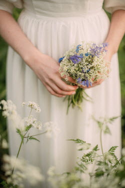 Rebecca Stice WOMAN IN WHITE HOLDING BUNCH OF FLOWERS OUTDOORS