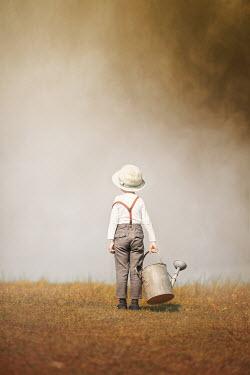 Anna Buczek LITTLE BOY IN HAT WITH WATERING CAN IN FIELD