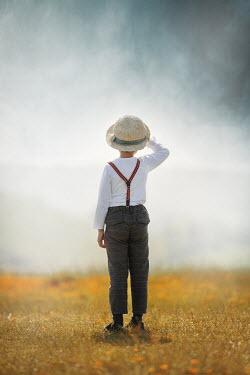 Anna Buczek LITTLE BOY IN HAT STANDING IN SUMMERY COUNTRYSIDE