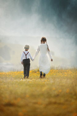 Anna Buczek YOUNG BOY AND GIRL WALKING IN FIELD HOLDING HANDS