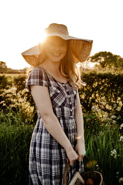 Esme Mai HAPPY GIRL WITH HAT AND PLAID DRESS IN SUMMERY COUNTRYSIDE