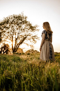 Esme Mai BLONDE WOMAN WITH APRON IN SUNLIT FIELD