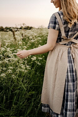 Esme Mai BLONDE WOMAN WITH APRON BY FIELD OF WHITE FLOWERS