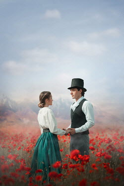 Ildiko Neer Historical couple standing in poppy field by mountains